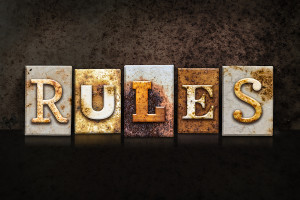 "The word ""RULES"" written in rusty metal letterpress type on a dark textured grunge background."